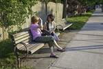 Two women sit and chat on a bench on Shrewsbury Street in Worcester, MA