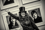 Woman with top hat gestures excitedly in front of Beatles photos