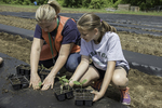 Fifth grader and her teacher working in a community garden