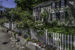 Flowers spill over a picket fence at a house in Concord, MA