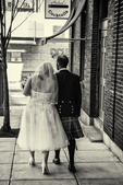 Bride and groom walking down a sidewalk in a city just after marriage ceremony
