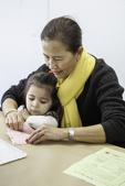 Teacher helping young girl make art