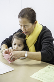 Teacher showing young girl how to make art