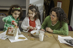 Mom and two daughters working on a gingerbread house