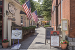 Flags fly over an allry that leads to shops and restaurants in Stockbridge, MA