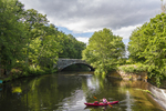 A red canoe in the Blackstone River in Uxbridge, MA