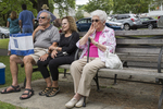Three people sitting on a bench at an arts and crafts show in Lenox, MA