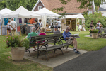 People sitting on a bench at an arts and crafts show in Lenox, MA