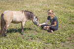 Woman sitting with her miniature horse in the pasture
