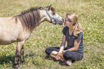 Miniature horse kissing owner