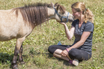 Woman sitting in a field with her miniature horse