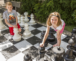 Kids playing a very large game of chess