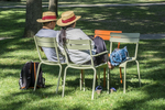 Two people sitting in chairs in Harvard Yard with straw hats and a red ribbon