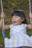Two year old swinging on a swing laughing