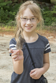 Little girl shows a feather that she found on the ground during a nature education workshop for kids