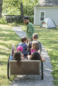 Man pulling a wagon with several children in it