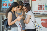 Three female students look at a message on a smartphone in Harvard Square, Cambridge, MA