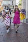 A woman in a pink dress walks with her daughter along Mass Ave in Cambridge, MA