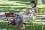 Woman sitting in Harvard Yard using her smartphone
