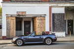 BMW convertible parked in front of a condemned building in Gardner, MA