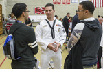 High school students at a college fair talking with a navy recruiter. #10