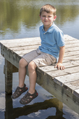 Little six year old boy sitting on a dock in the summer