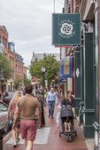 People stroll down a street in Portland Maine's Old Port