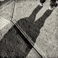 A shadow of a person standing on the sidewalk on Highland Street