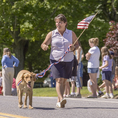 Woman and her dog (Anne Gobi, MA State Senator)  marching in the July 4th parade in Petersham, MA