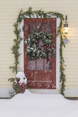 A wreath and a pine swag adorn a red door on an old house