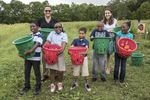 Kids holding baskets of vegetables that they just picked
