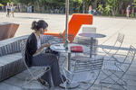 Woman using her laptop and mobile phone at an outdoor table in Harvard Square