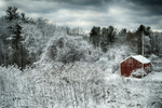 Red barn in the valley on a snowy morning