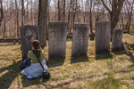 Photographer taking a photograph of a grave stone in an old cemetery in the center of Petersham, MA