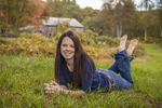 Teenage girl sitting in a farm meadow
