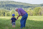 Boy and his grandfather in a farm meadow