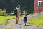 Mother and son walking up a driveway to the barn