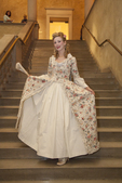 Woman dressed in a fancy gown descends a stairway at the Worcester Art Museum