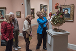 A docent explains one of the floral displays to Worcester Art Museum visitors