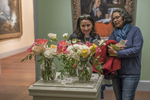 Two women looking at a floral display - display in focus