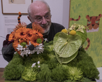 Ed Emberley making a funny face behind a floral display created to match one of his drawings