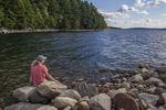 Woman sitting on the shoreline at the Quabbin Reservoir