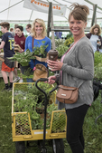 Two women with plants that they have just purchased at a plant sale.