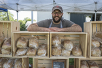 A baker with his bread at an outdoor market
