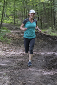 A woman running on a woods trail