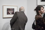 Man reading the caption that goes with the photograph in a gallery