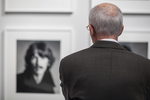 Man looking at a black and white photograph in a gallery