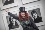 Woman celebrating in front of photographs of the music group the Beatles