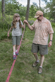 Young girl and her dad walking on a tight rope
