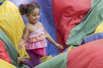 Young girl playing in a colorful parachute